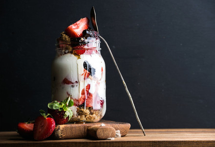 Yogurt oat granola with strawberries  mulberries  honey and mint leaves in tall glass jar on black backdrop