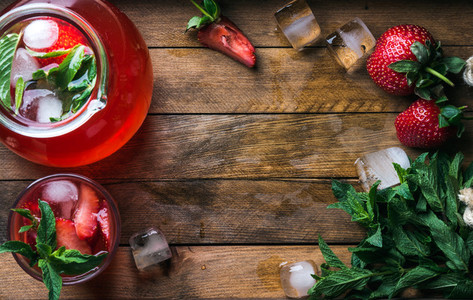 Homemade strawberry mint lemonade served with fresh berries and ice over wooden background  top view  copy space