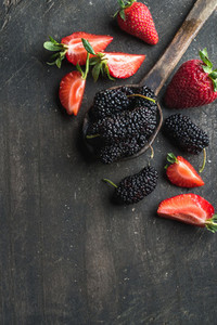 Berries on dark wooden background Fresh strawberries and mulberries in rustic cooking spoon