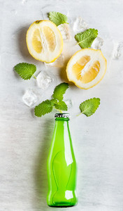 Green lemonade bottle with ingredients and ice cubes on steel background