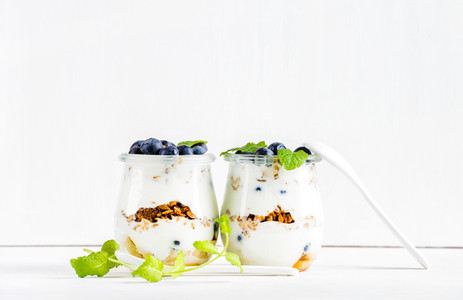 Yogurt oat granola with jam  blueberries and green mint leaves in glass jars on white backdrop
