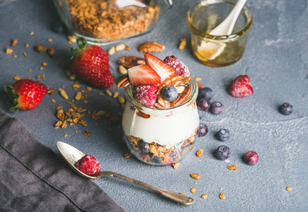Yogurt oat granola with fresh berries  nuts  honey and mint leaves in glass jar on grey concrete textured backdrop