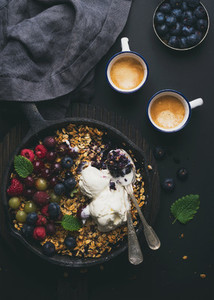 Healthy breakfast  Oat granola crumble with fresh berries  seeds and ice cream in iron skillet pan on dark wooden board  coffee over black backdrop