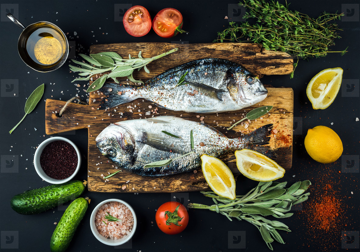 Fresh uncooked dorado or sea bream fish with lemon  herbs  oil  vegetables and spices on rustic wooden board over black backdrop
