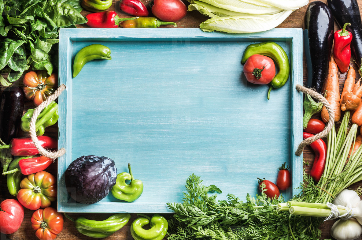 Fresh raw ingredients for healthy cooking or salad making with blue wooden tray in center  top view  copy space