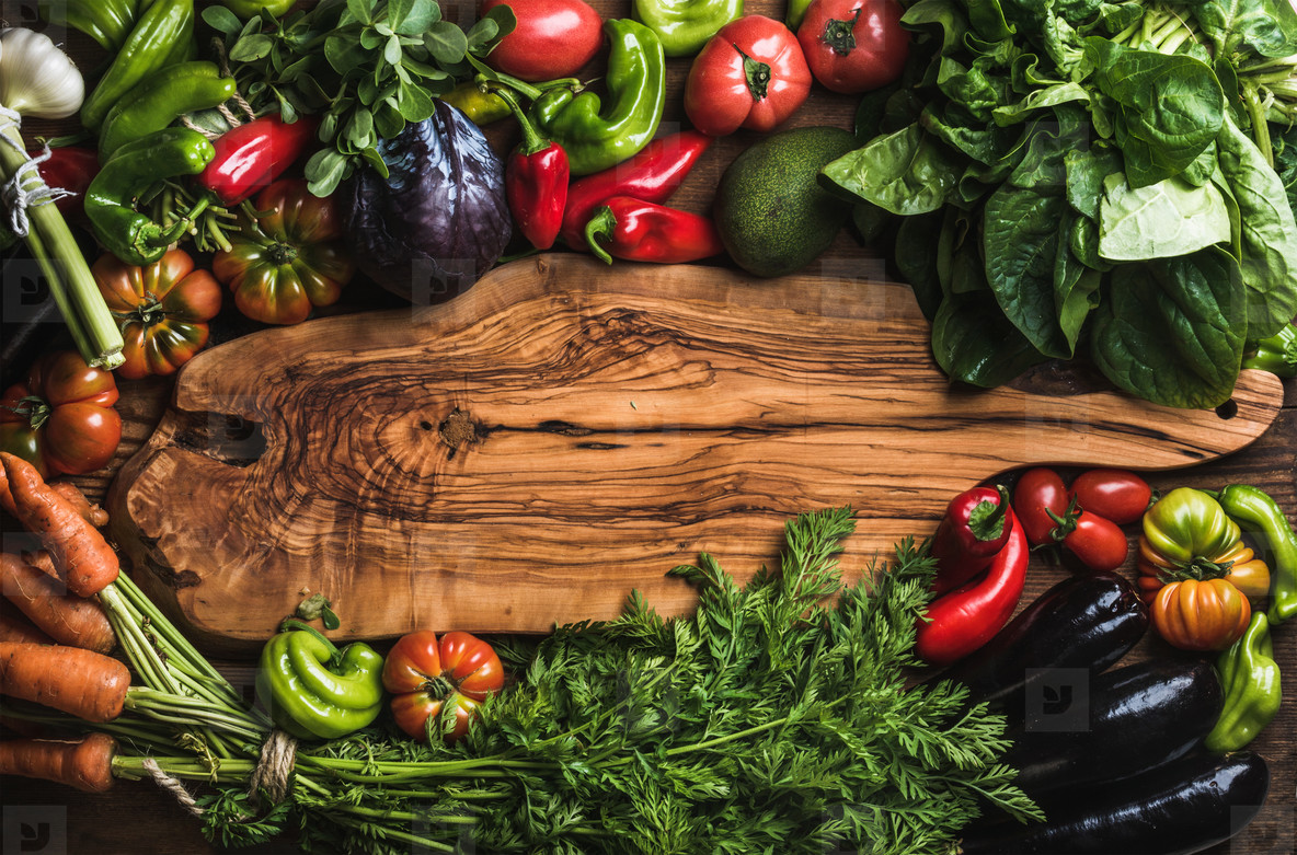 Fresh raw vegetable ingredients for healthy cooking or salad making with rustic olive wood board in center