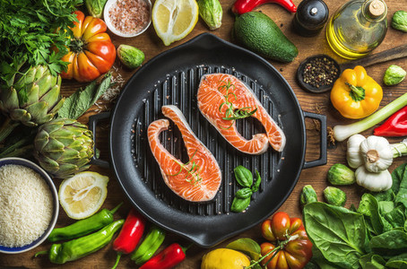 Dinner cooking ingredints  Raw uncooked salmon fish with vegetables  rice  herbs  spices and oil in iron grilling pan over rustic wooden background