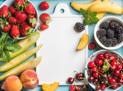 Healthy summer fruit variety  Sweet cherries  strawberries  blackberries  peaches  bananas  melon slices and mint leaves on blue backdrop with white ceramic board in center