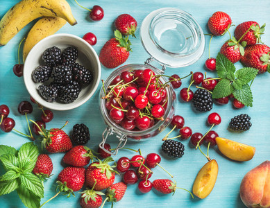 Healthy summer fruit variety  Sweet cherries  strawberries  blackberries  peaches  bananas and mint leaves on blue backdrop