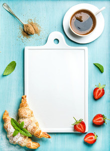 Breakfast or dessert set  Freshly baked croissants with strawberries and cup of coffee over blue background  white ceramic board in center