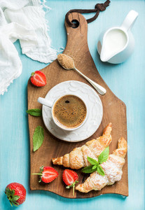 Breakfast or dessert set  Freshly baked croissants with strawberries  cup of coffee and milk in creamer on brown wooden board