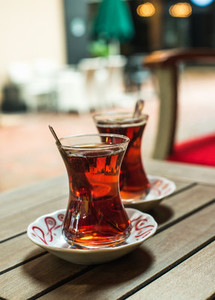 Turkish tea in traditional tulip glasses on table of street cafe