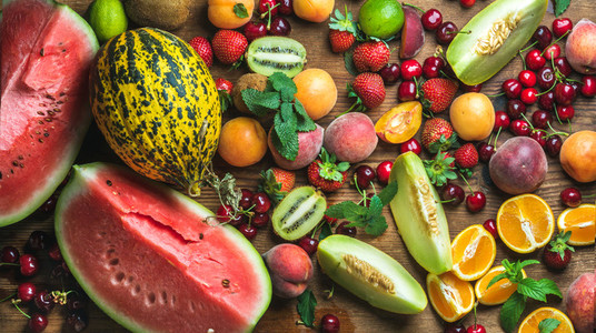 Various colorful tropical fruit selection on rustiv wooden background