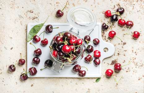Sweet cherry in glass jar on white board over concrete background