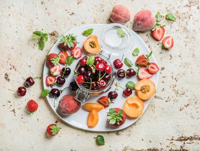 Healthy summer fruit variety  Sweet cherries  strawberries  blackberries  peaches  bananas and mint leaves on blue backdrop