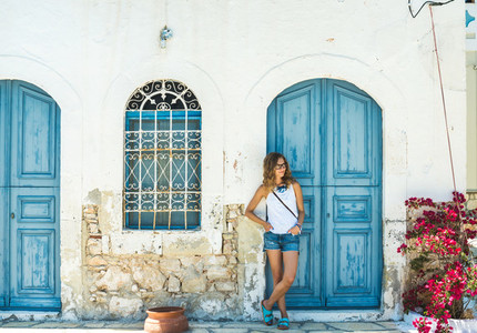 Young blond woman at typical greek traditional town with colorful buildings on Kastelorizo Island  Greece