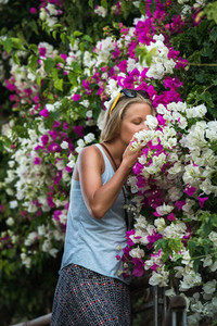 Young blond woman tourist smelling flowers in the old town center of Alanya