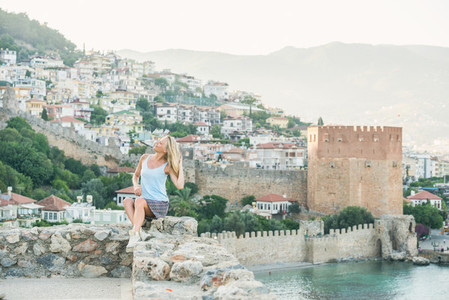 Young blond woman tourist sitting on ancient fortress wall of Alanya castle