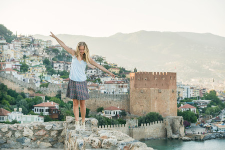 Young blond woman tourist balancing on ancient fortress wall of Alanya castle