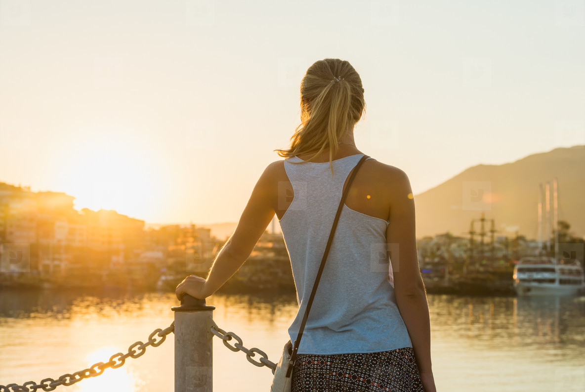 Young blond woman watching sunset
