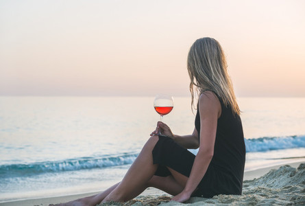 Young blond woman enjoying glass of rose wine on beach by the sea at sunset