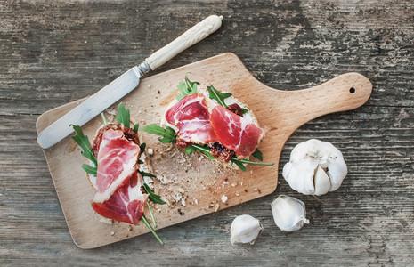 Brushetta set with smoked meat  arugula  garlic and dried tomato