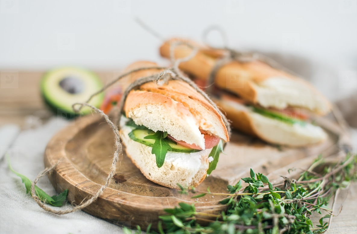 Salmon  avocado and thyme sandwiches in baguette tied up with decoration rope on a rustic wooden board over rough wood background