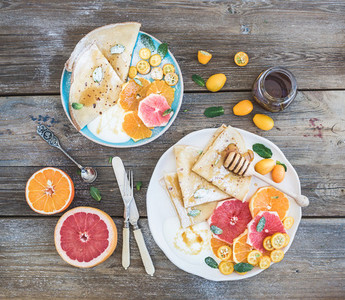 Spring vitamin breakfast set  Thin crepes or pancakes with fresh grapefruit  orange  kumquat  honey  cream and mint leaves over a rustic wood background