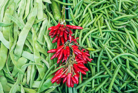 Fresh string beans and red chili peppers on a market stall