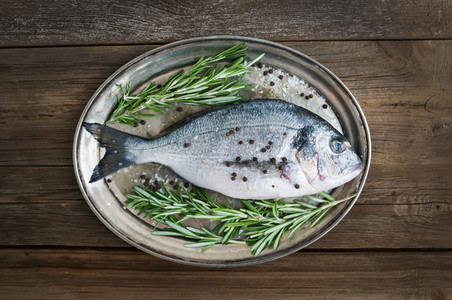 Fresh sea fish  dorado  on a metal dish with rosemary and spices