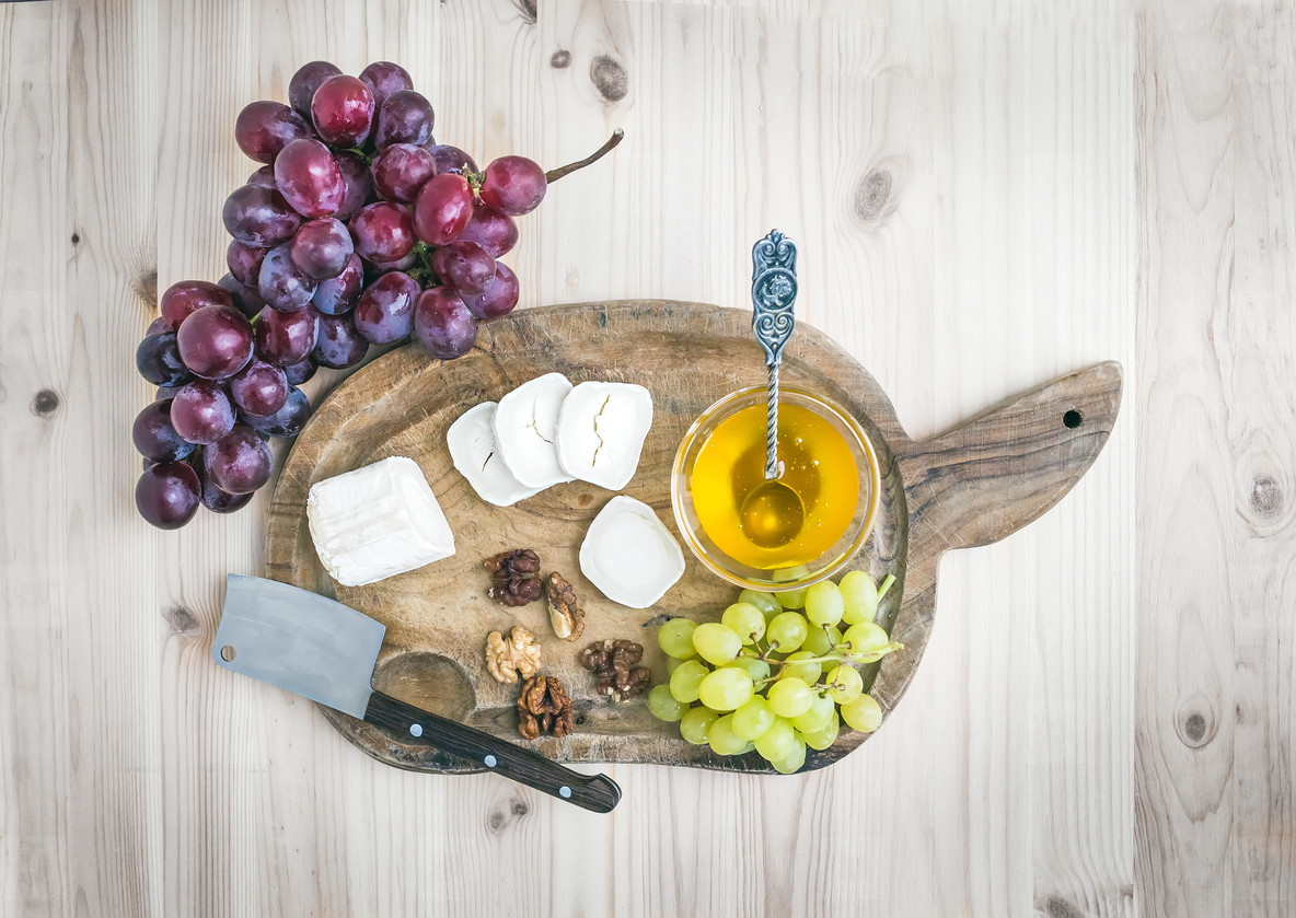 Goat brie cheese with fresh grapes and honey on a rustic wooden