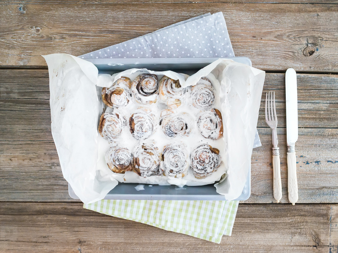 Cinnamon buns with cream cheese icing in a baking dish over a ru