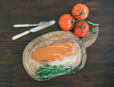 Chicken carpaccio  tomatoes and rosemary on a rustic wooden boar