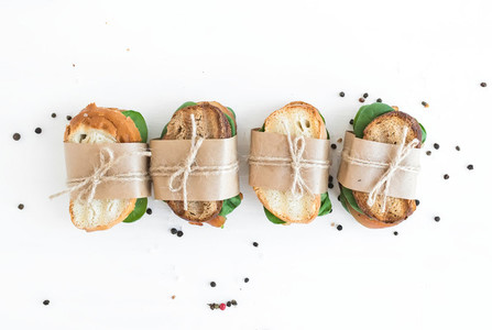 Chicken and spinach sandwiches wrapped in craft paper over a whi