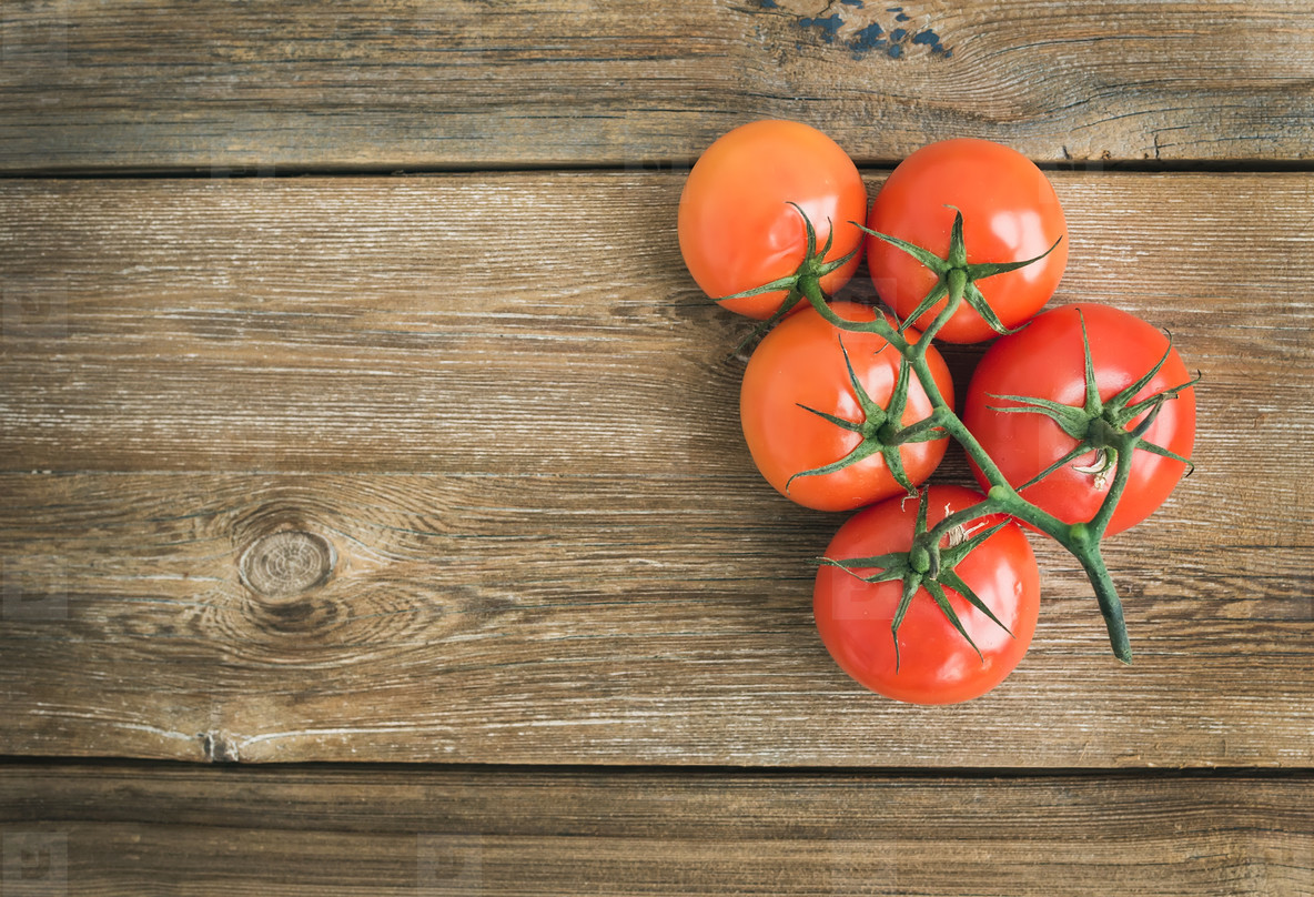 Bunch of fresh ripe red tomatoes over a rustic wood background w