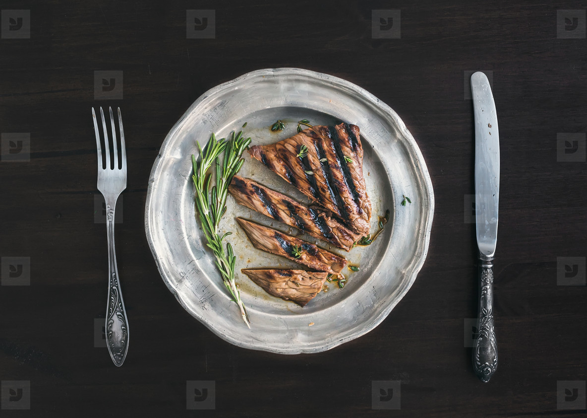 Beef steak cut into pieces with rosemary  knife and fork on a vi