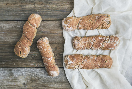 Freshly baked rustic  village bread baguettes set on rough woo