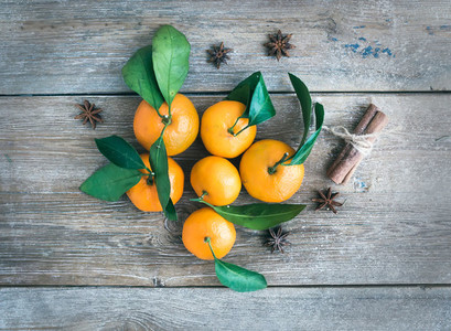 Fresh mandarines with cinnamon sticks and anise stars over a rou