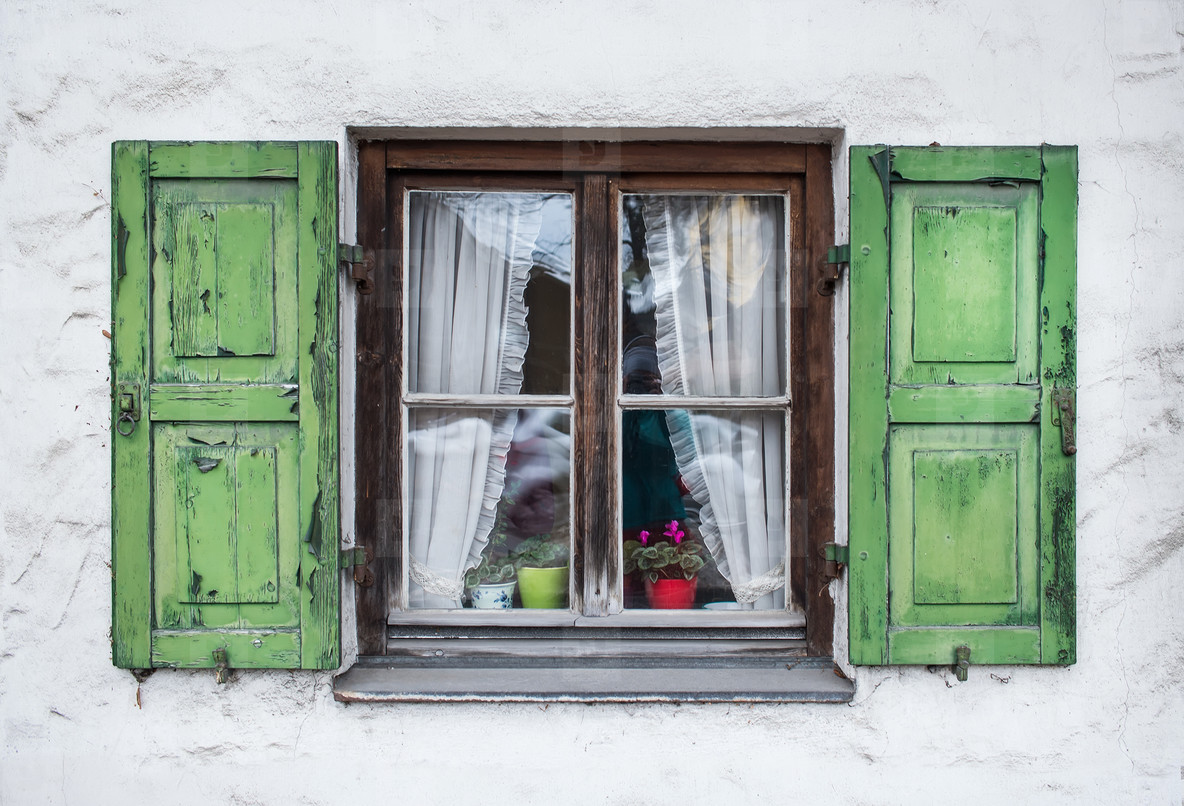 Authentic window with green wooden shuttters in a small town of