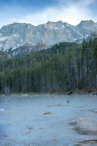 Frozen forest lake in Bavarian Alps near Eibsee lake winter
