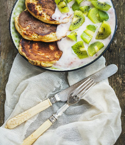 Rustic breakfast set with pancakes with strawberry yogurt and fr