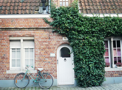 Oldstyle bicycle in front of the red brick wall of a building pa