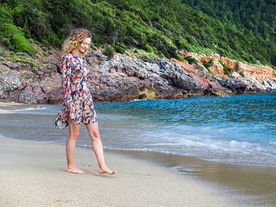 A young blond haired woman walking along the beach