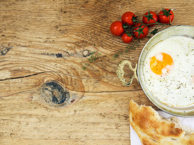 Breakfast set fried egg  bread and cherry tomatoes on a wooden