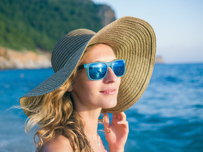 A girl in sunglasses and a hat on the beach