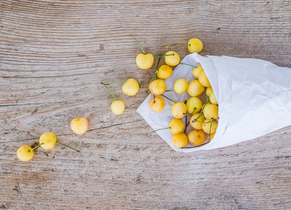 Yellow sweet cherries in a paperbag on a rought wood surface