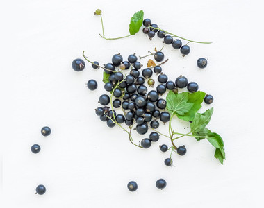 Black currant berries and green leaves over a white wooden sufra