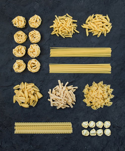 Different types of Italian uncooked pasta on black slate stone background  top view