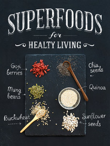 Superfoods on black chalkboard background goji berries  chia  mung beans  buckwheat  quinoa  sunflower seeds  Top view  white lettering
