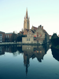 View of cathedral the center Bruges Belgium and its reflection in water